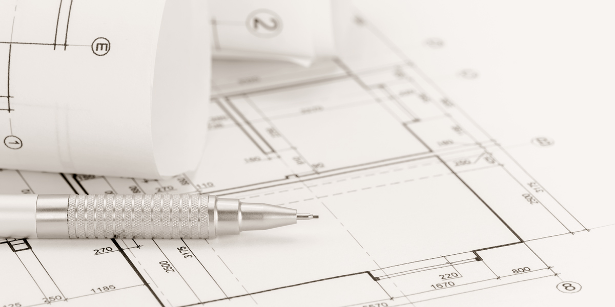 architect workspace with rolled floor plans and blueprints